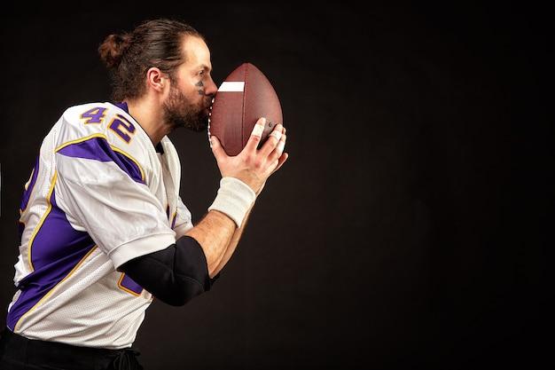 Крупным планом портрет агрессивного игрока американского футболиста, который молится на своем мяче