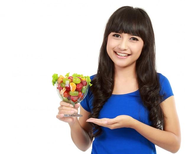Портрет крупного плана привлекательной молодой женщины есть фруктовый салат