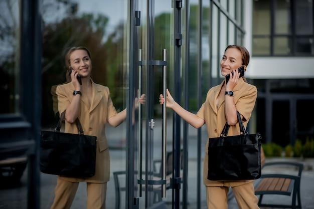 사무실 건물 밖에 서서 휴대 전화를 말하는 사업가의 근접 촬영 초상화.