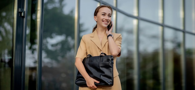 Макрофотография портрет бизнес-леди, стоя вне офисного здания и говоря мобильный телефон.
