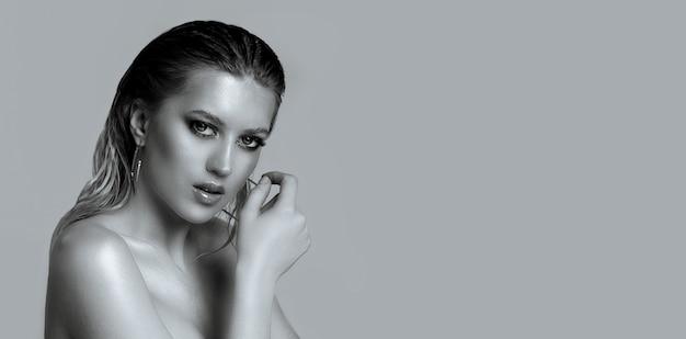 灰色の背景の上に濡れた髪と裸の肩を持つエレガントな若い女性のクローズアップの肖像画。空きスペース
