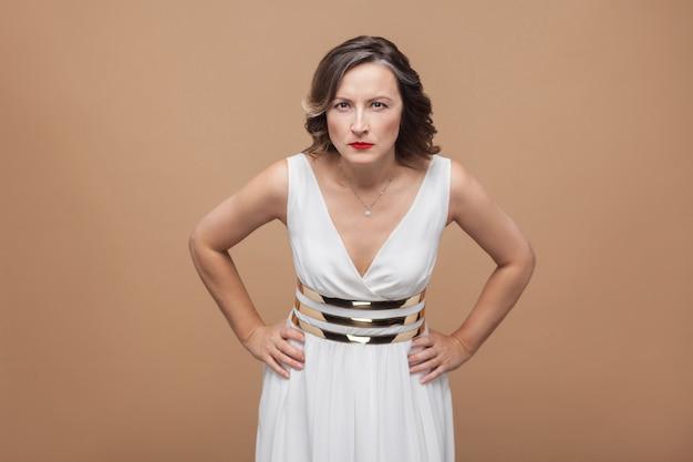 カメラを見ている怒っている女性のクローズアップの肖像画。白いドレス、赤い唇、暗い巻き毛の髪型で感情的に表現する女性。スタジオショット、屋内、ベージュまたは薄茶色の背景に分離