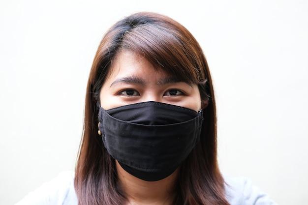 黒の保護医療マスクを身に着けているアジアの女性の顔のクローズアップの肖像画