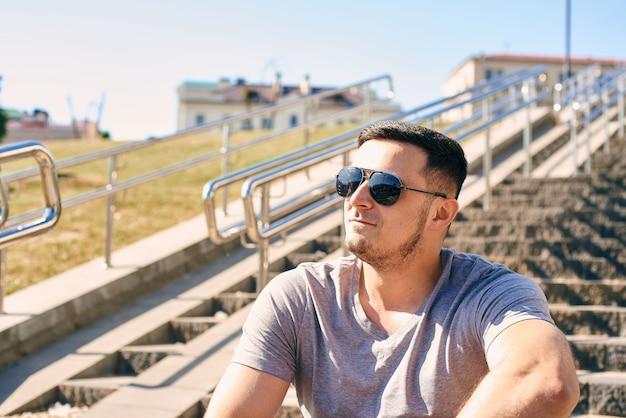 선글라스 회색 티셔츠를 입고 운동 잘 생긴 젊은 백인 갈색 머리 남성의 근접 촬영 초상화