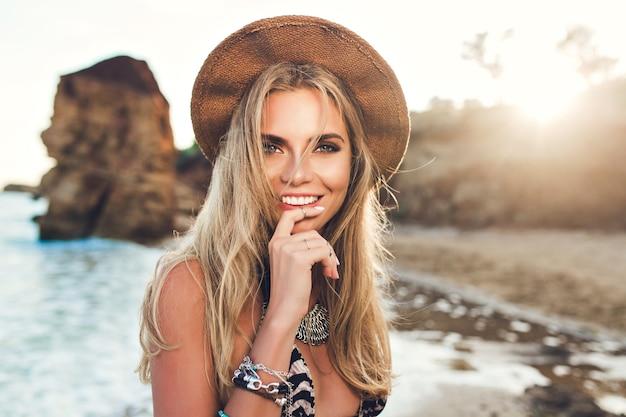 夕日を背景に岩のビーチでポーズをとって長い髪を持つ魅力的なブロンドの女の子のポートレート、クローズアップ。彼女は唇に指を保持し、カメラに笑顔を保持します。