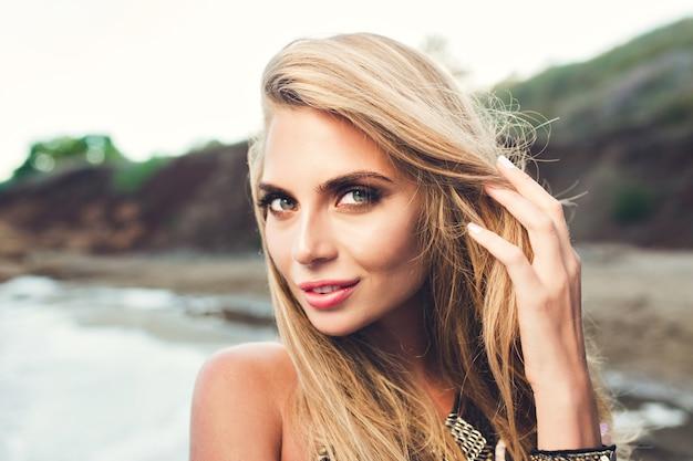 岩の多いビーチでポーズ長い髪の魅力的なブロンドの女の子のポートレート、クローズアップ。彼女は髪に触れてカメラを見ています。