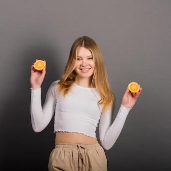 Портрет крупным планом привлекательной кавказской улыбающейся женщины-блондинки изолированной на серой студии, зубастой улыбкой на лице, смотрящей на зуб камеры апельсиновый лимон