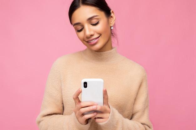 Портрет крупным планом привлекательной милой улыбающейся молодой брюнетки в бежевом теплом свитере, стоя изолированной