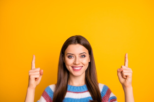 두 집게 손가락을 가리키는 매력적인 기쁜 여자의 근접 촬영 초상화