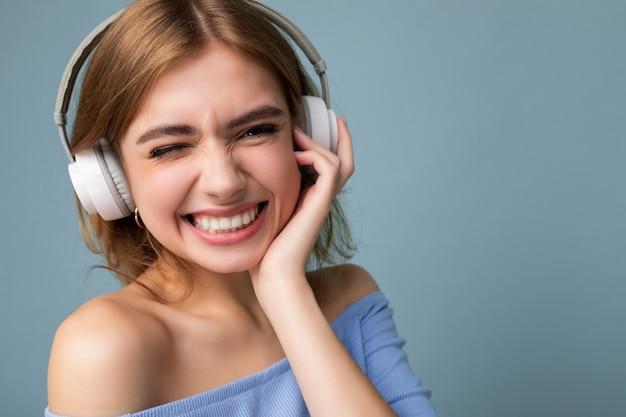 파란색 자르기 탑을 입고 매력적인 행복 웃는 젊은 금발의 여자의 근접 촬영 초상화에 고립