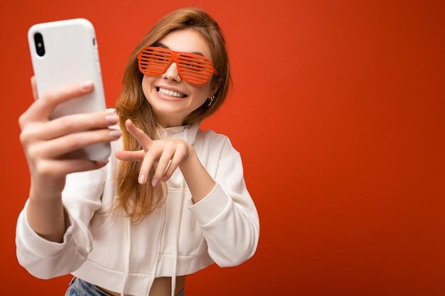세련 된 흰색 까마귀를 입고 매력적인 긍정적인 웃는 젊은 금발 여자의 근접 촬영 초상화와