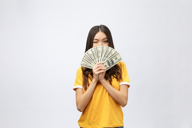 Портрет крупным планом красивой азиатской женщины, держащей деньги
