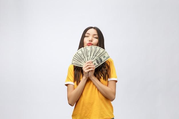 お金を保持している美しいアジアの女性のクローズアップの肖像画