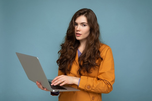 보고 넷북 컴퓨터를 들고 아름 다운 차분한 brunet 곱슬 젊은 여자의 근접 촬영 초상화