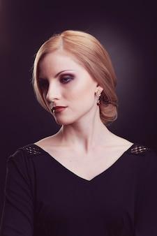 黒の背景にブロンドの髪を持つ美しい女性モデルのクローズアップの肖像画。