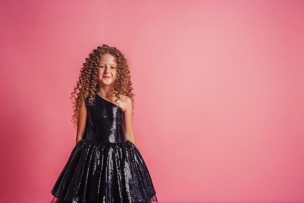 Крупным планом портрет красивой девушки в черном платье на розовом фоне в студии, улыбаясь и позирует