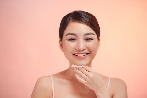 ヌードメイクで美しい健康な女の子のクローズアップの肖像画は、吸油ティッシュシートで完璧な柔らかい肌を掃除します