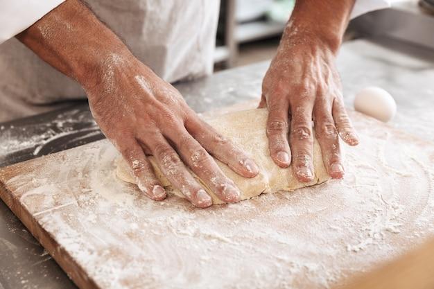 빵집이나 부엌에서 테이블에 빵 반죽을 만드는 아름다운 남성 손의 근접 촬영 초상화