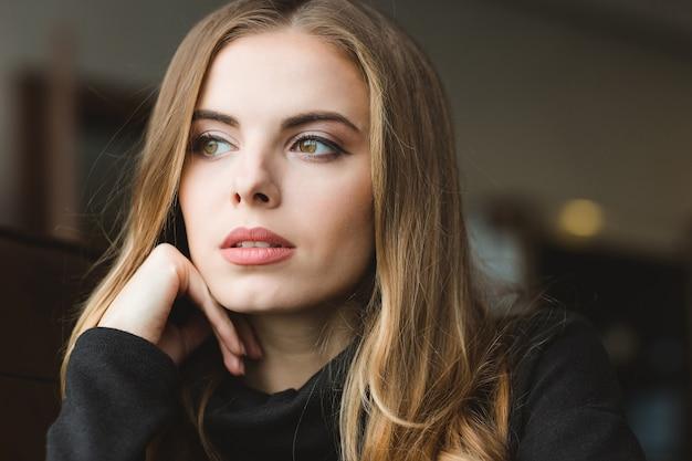 Портрет крупным планом красивой задумчивой молодой блондинки, глядя в сторону