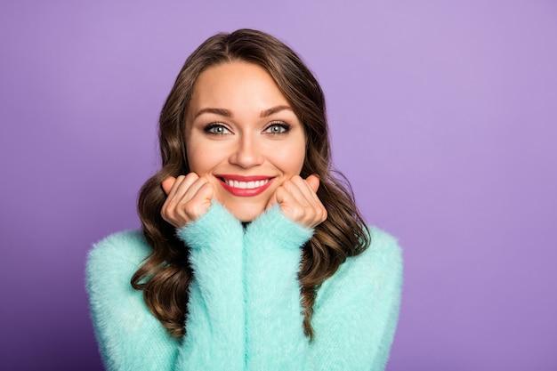 美しいきれいな女性のクローズアップの肖像画は頬骨に腕を持って歯を見せる笑顔はティールのふわふわファジーパステルセーターの暖かさの柔らかさをお楽しみください。
