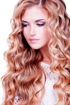 옆으로-흰색 bakground에 고립 된 찾고 긴 금발 곱슬 머리를 가진 아름 다운 관능적 인 여자의 근접 촬영 초상화.