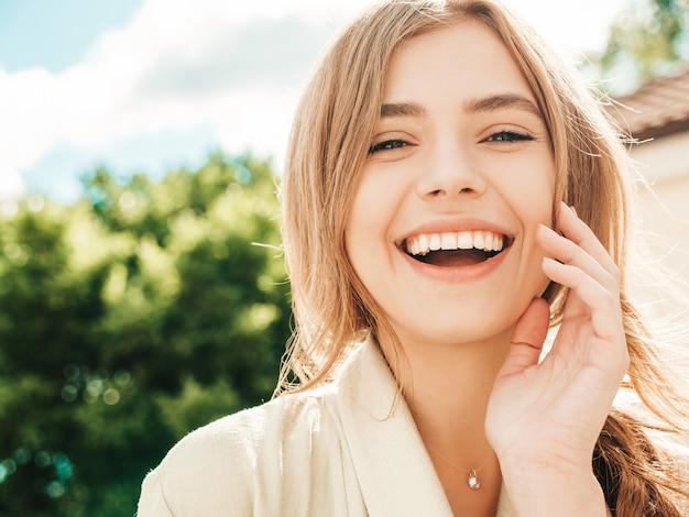 夏の流行に敏感な服に身を包んだ美しい笑顔の金髪モデルのクローズアップの肖像画。通りでポーズをとるトレンディな女の子