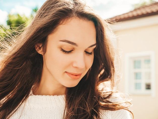 美しい笑顔のブルネットモデルのクローズアップの肖像画。通りでポーズをとるトレンディな女性
