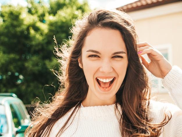 美しい笑顔のブルネットモデルのクローズアップの肖像画。通りでポーズをとるトレンディな女の子