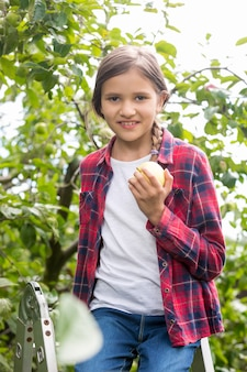 Портрет крупным планом красивой улыбающейся девушки в клетчатой рубашке, позирующей в саду и кусающей яблоко
