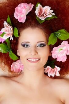 髪に色とりどりの花で美しい笑顔赤毛生inger女性顔のクローズアップの肖像画