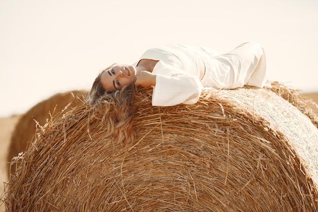 Портрет крупного плана красивой усмехаясь женщины. блондинка на тюке сена. пшеничное поле на заднем плане.