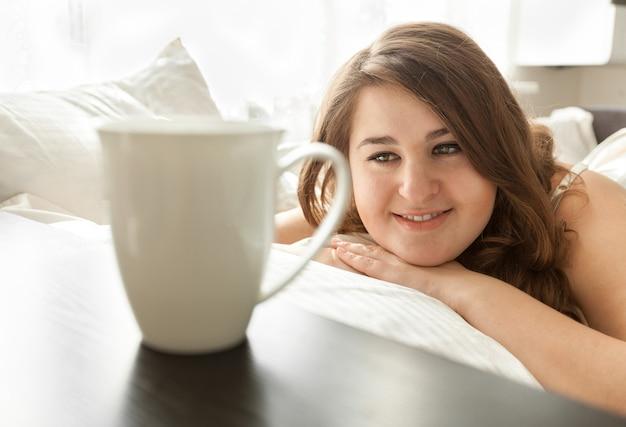 Портрет крупным планом красивой женщины, лежащей в постели и смотрящей на чашку