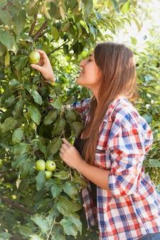 Портрет крупным планом красивой женщины, собирающей зеленое яблоко с дерева