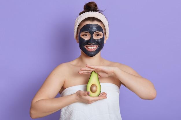 이국적인 아보카도 과일을 들고 벌거 벗은 어깨를 가진 아름 다운 여자의 근접 촬영 초상화