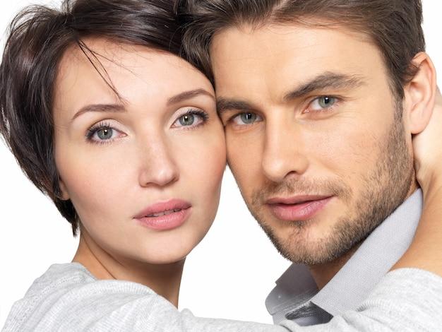 美しい若いカップルのクローズアップの肖像画。カメラを見ている魅力的な男性と女性