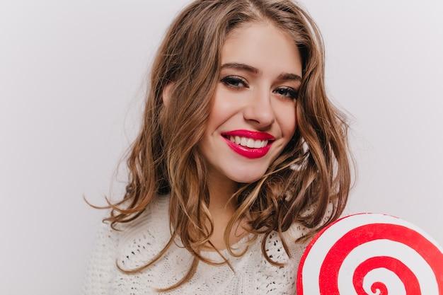 Портрет крупным планом красивой молодой девушки в отличном настроении, позирующей с леденцом на белой стене
