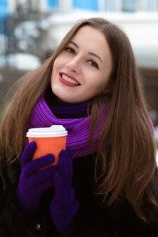 커피 한잔과 함께 포즈를 취하는 아름다운 젊은 모델의 근접 촬영 초상화
