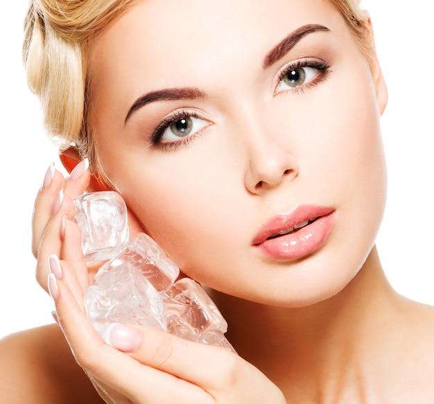 美しい若い女性のクローズアップの肖像画は、顔に氷を適用します。スキンケアのコンセプト。白で隔離。