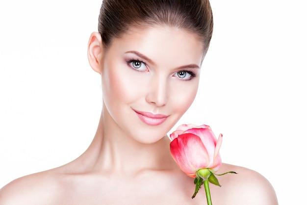 Крупным планом портрет красивой молодой женщины со здоровой кожей и цветком возле лица - изолированные на белом.