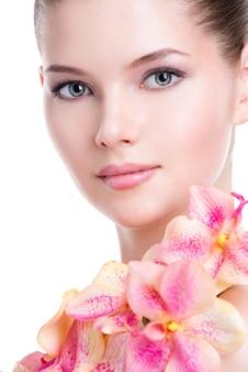 健康な肌と体にピンクの花を持つ美しい若い女性のクローズアップの肖像画-白で隔離。