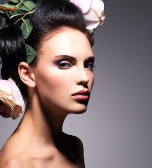 髪にピンクの花を持つ美しい若い女性のクローズアップの肖像画-灰色の背景に