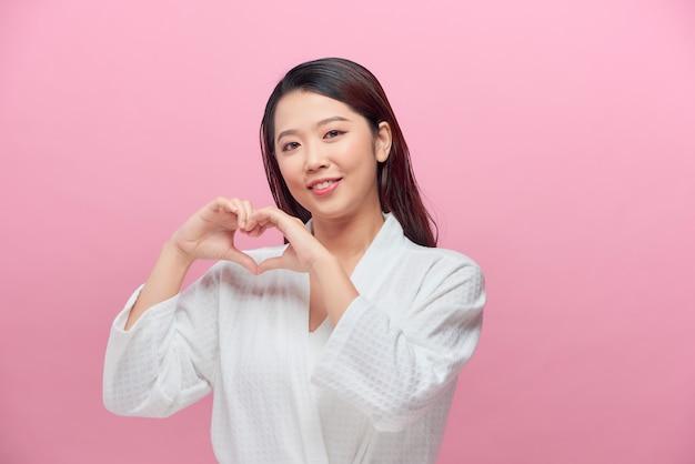 美容アジアの女性のクローズアップの肖像画は、健康的な完璧な肌の手ジェスチャーの心をクリア