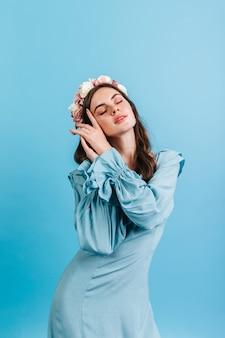 孤立した壁にサテンの青いドレスのブルネットのクローズアップの肖像画。バラの冠で官能的にポーズをとる女性。