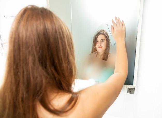 흐린 거울을 청소하고 반사를보고 갈색 머리 여자의 근접 촬영 초상화