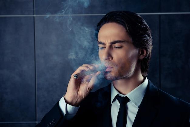 Крупным планом портрет жестокого молодого человека, курящего сигару