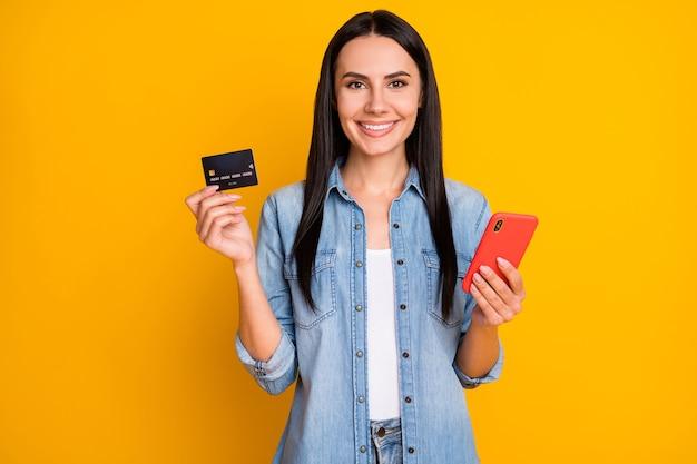 Портрет крупным планом очаровательной жизнерадостной девушки, держащей в руке карту сотового банка