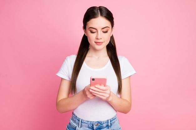 Портрет крупным планом очаровательной сосредоточенной девушки с помощью телефона