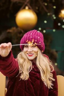 暖かい服を着て、クリスマスフェアで輝く線香花火を保持している陽気なブロンドの女性のクローズアップの肖像画