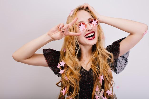 Портрет крупного плана жизнерадостной девушки с светлыми вьющимися волосами, прекрасно проводящих время на вечеринке, весело, празднуя, показывая мир. на ней черное платье, стильные розовые очки. изолированный ..