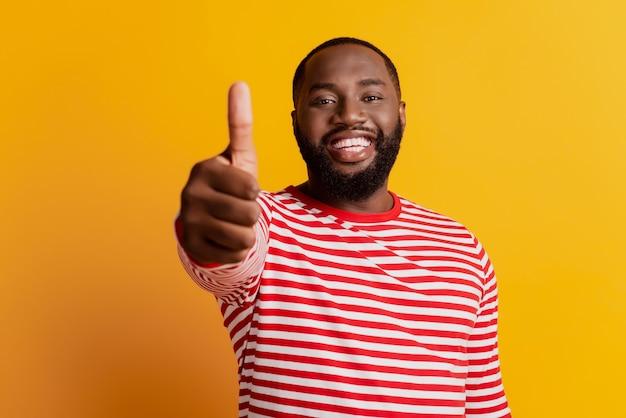Портрет крупным планом веселого позитивного молодого человека поднимает палец вверх